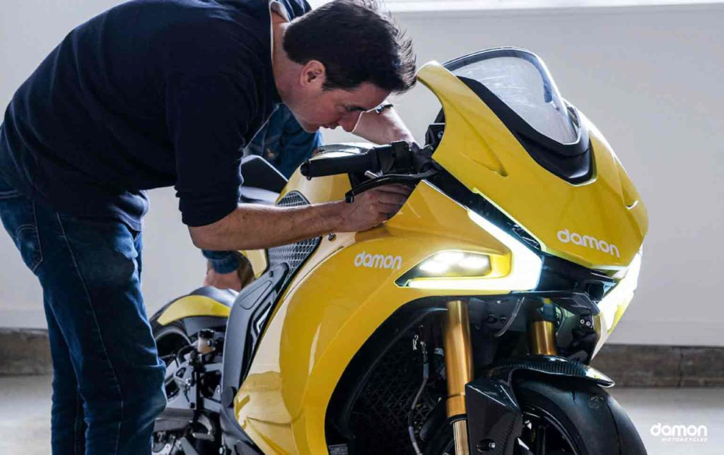 Man doing a small fixing to a yellow HyperSport Prototype