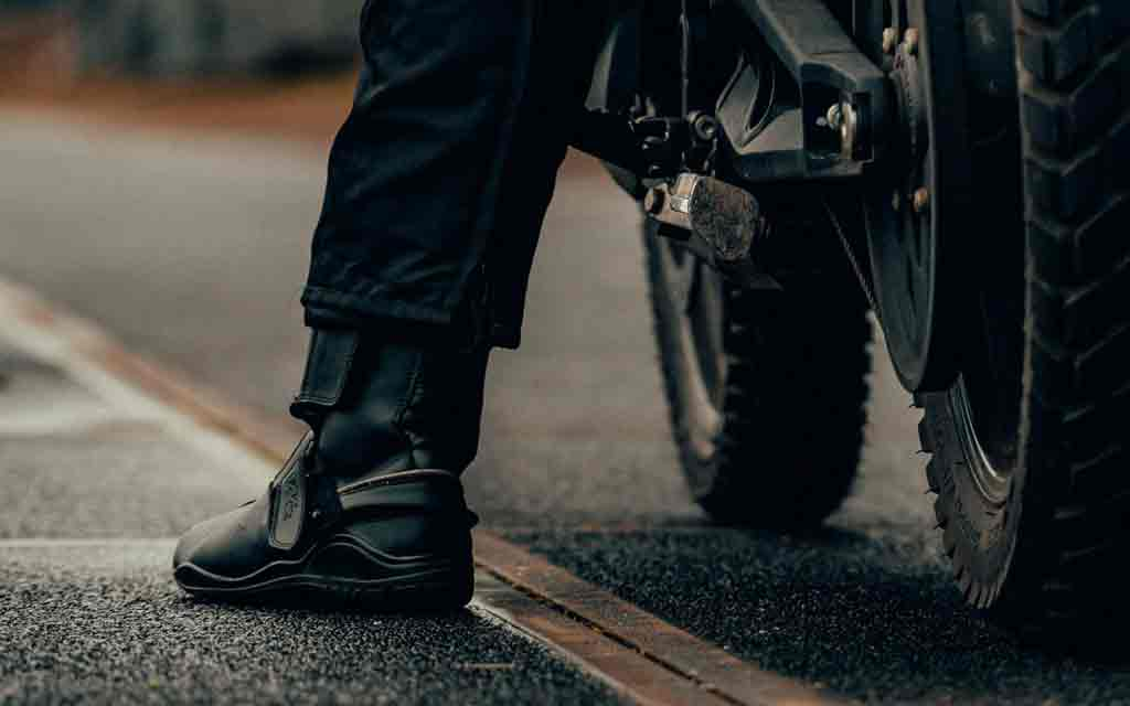 Close up of a motorcycle driver's leg standing on the floor while being on top of the bike