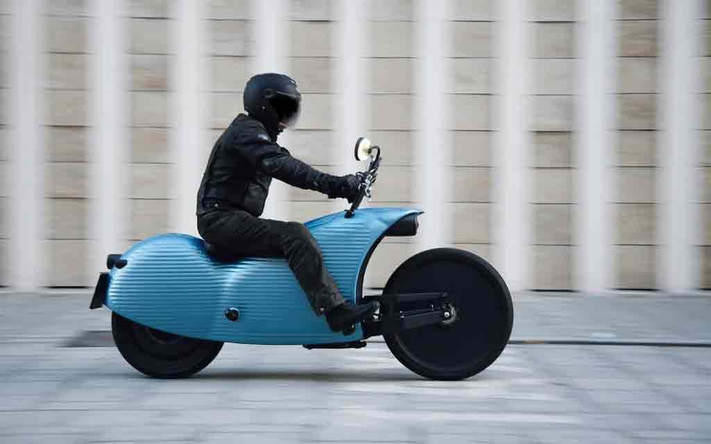 Driver on a blue Johammer Motorycle driving in the city