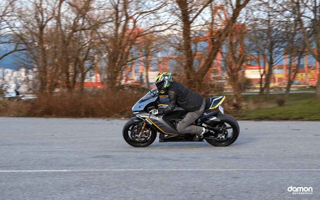 Motorcycle rider on a black outfit driving a sport motorcycle  on an road in the woods