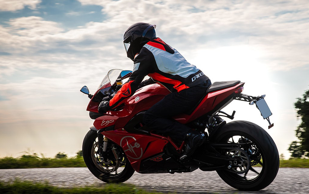 Rider on a red Energica Ego motorcycle driving on a highway
