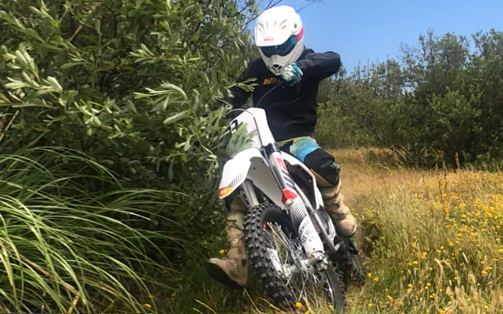 Jeff Sand, Design Director at Damon Motorcycle driving his racing bike in the woods