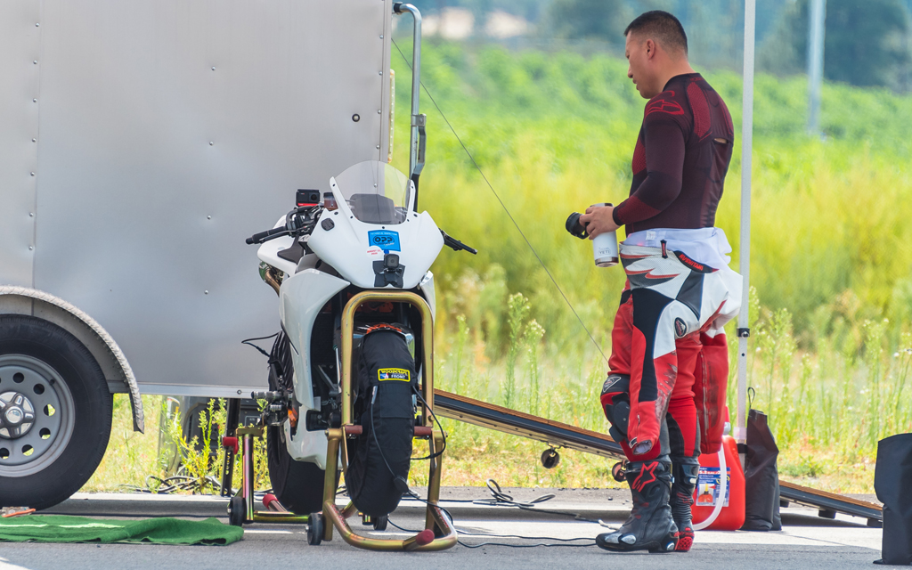 Dom Kwong, Co-founder and CTO of Damon Motorcycles preparing for a track day with a white Sport bike