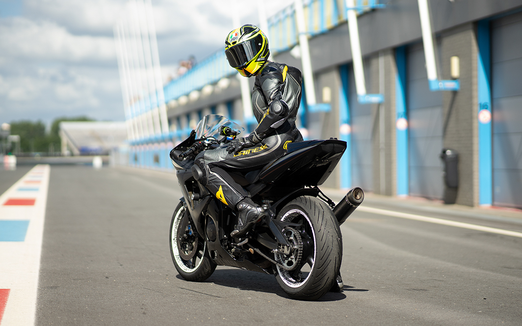 Woman on a black motorcycle gear outfit on a black sport bike in the city