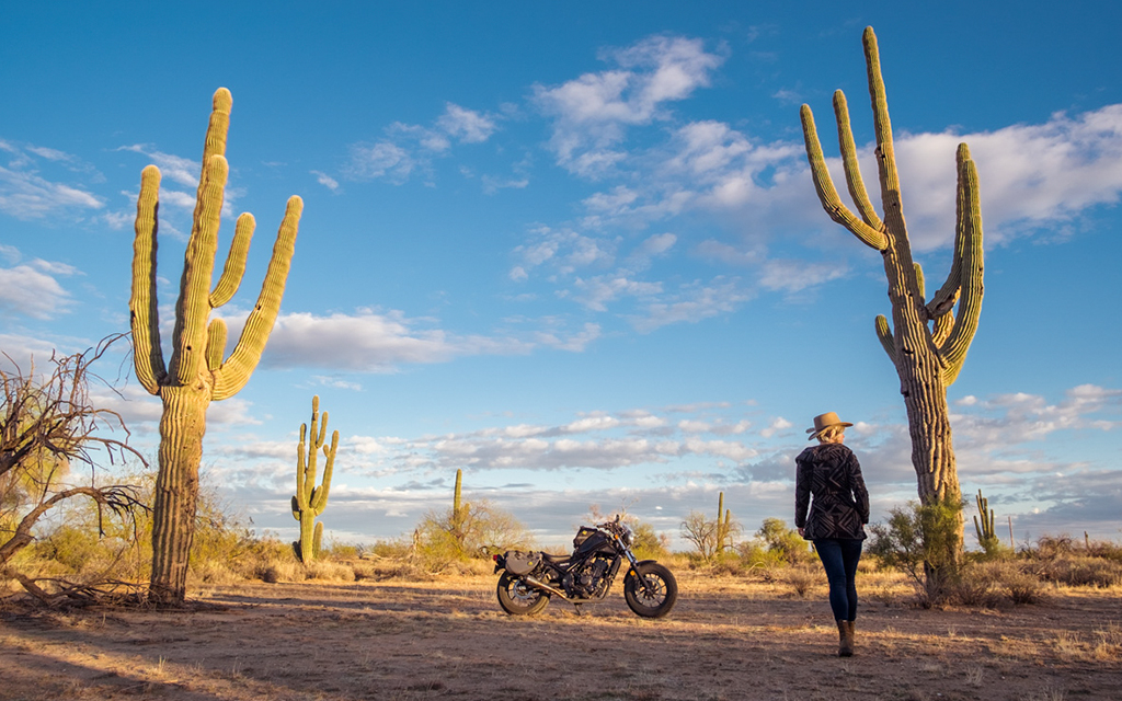 Blond woman in the desert wearing a black outfit walking towards her black dirty bike