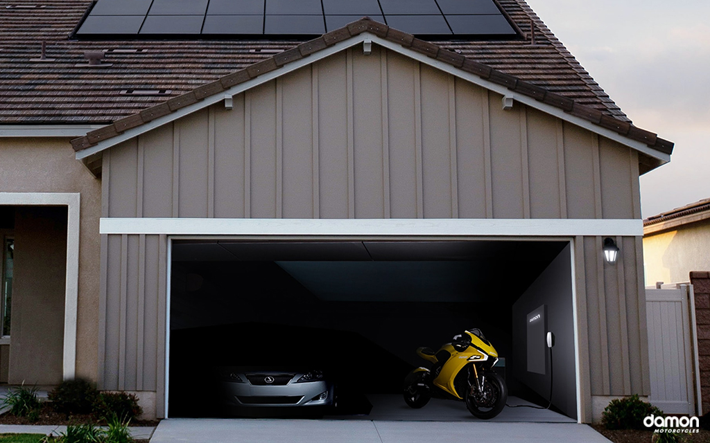Damon HyperSport HS connected up to an electric motorcycle charger next to a silver lexus in a home car garage