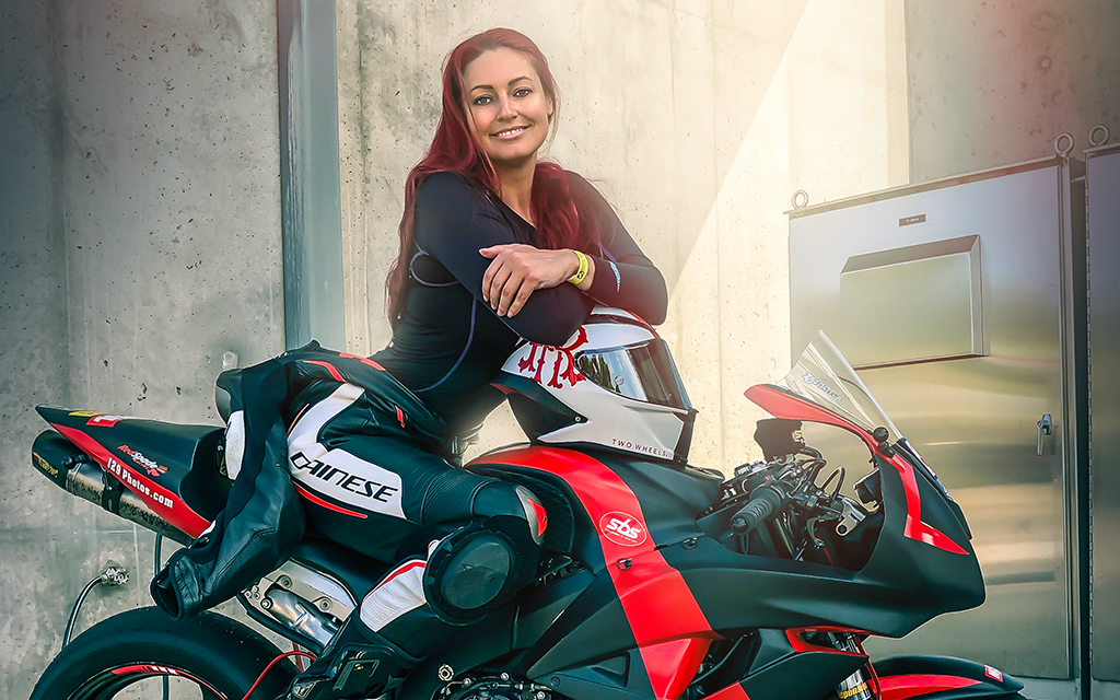 Redhaired woman in a black and red sport motorcycle with an industrial background