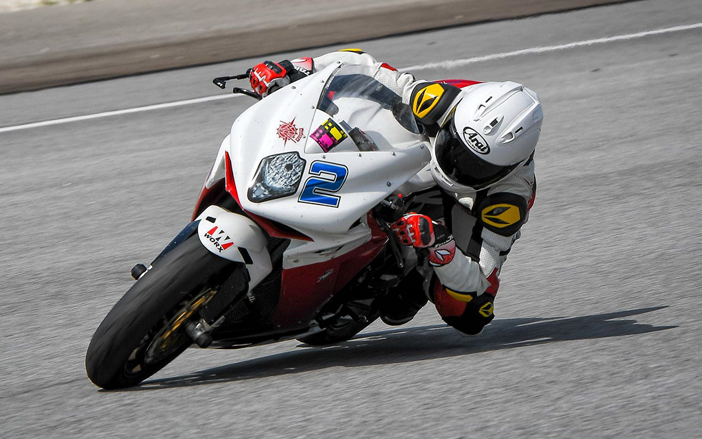 Female motorcycle rider riding a white sport bike at high speed