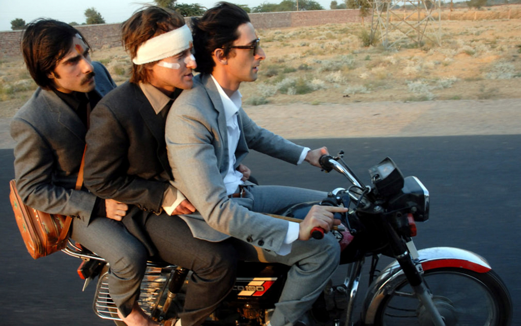 Scene from the Darjeeling Limited where three men wearing suits are on a motorcycle  driving on a road in the country side