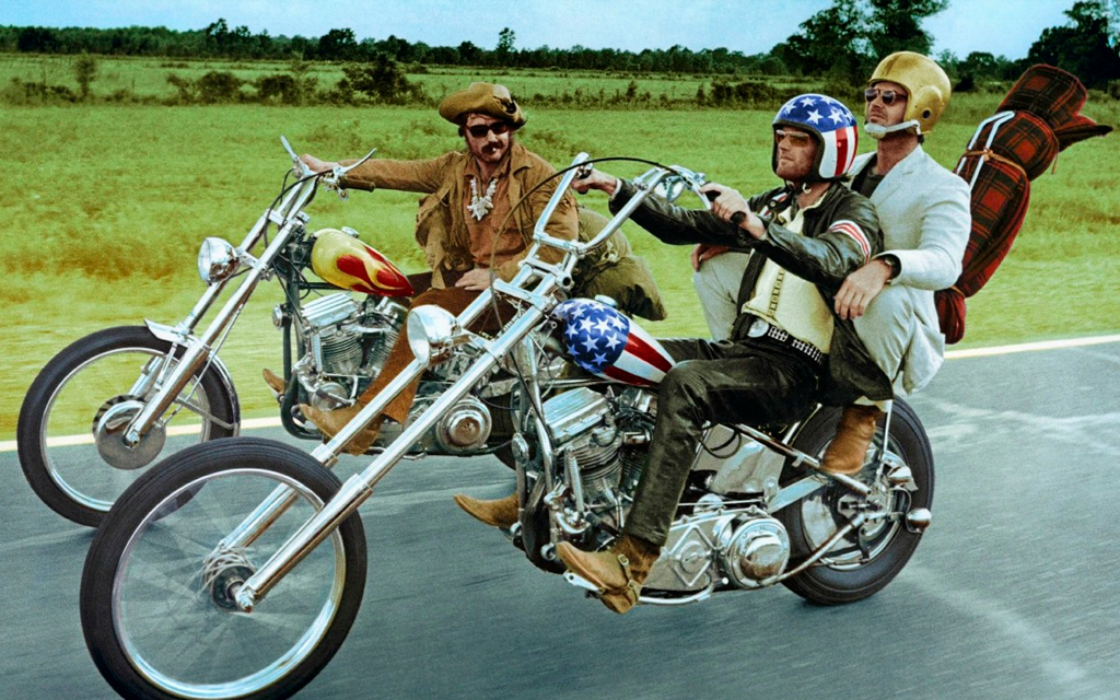 Scene of the movie Easy Rider when a group of friends are driving in a road in the country