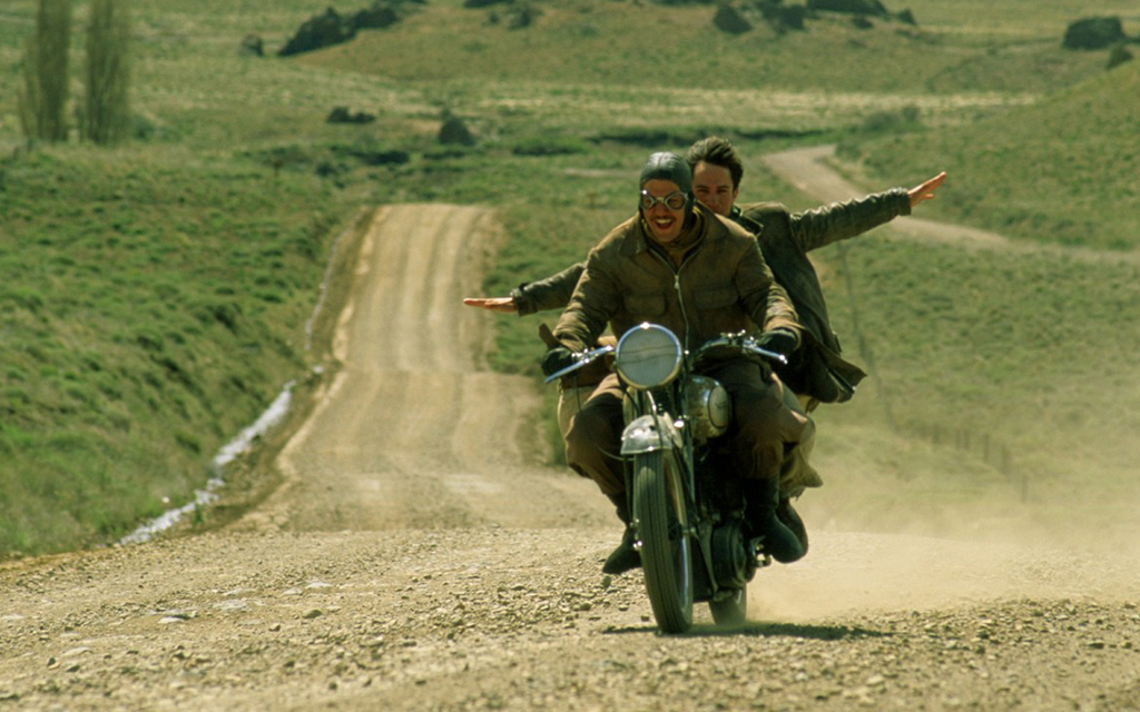 Scene of the movie The Motorcycle Diaries of two people on a motorbike riding on a dusty road in the country side
