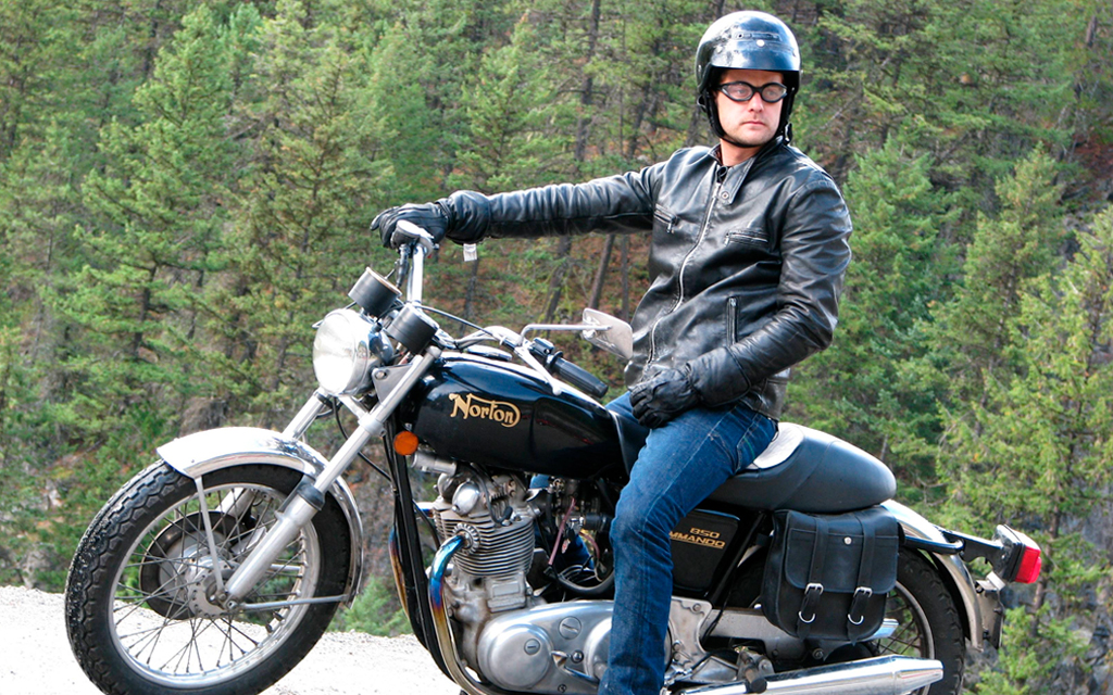 Motorcycle rider from the movie One Week on his black bike in the woods