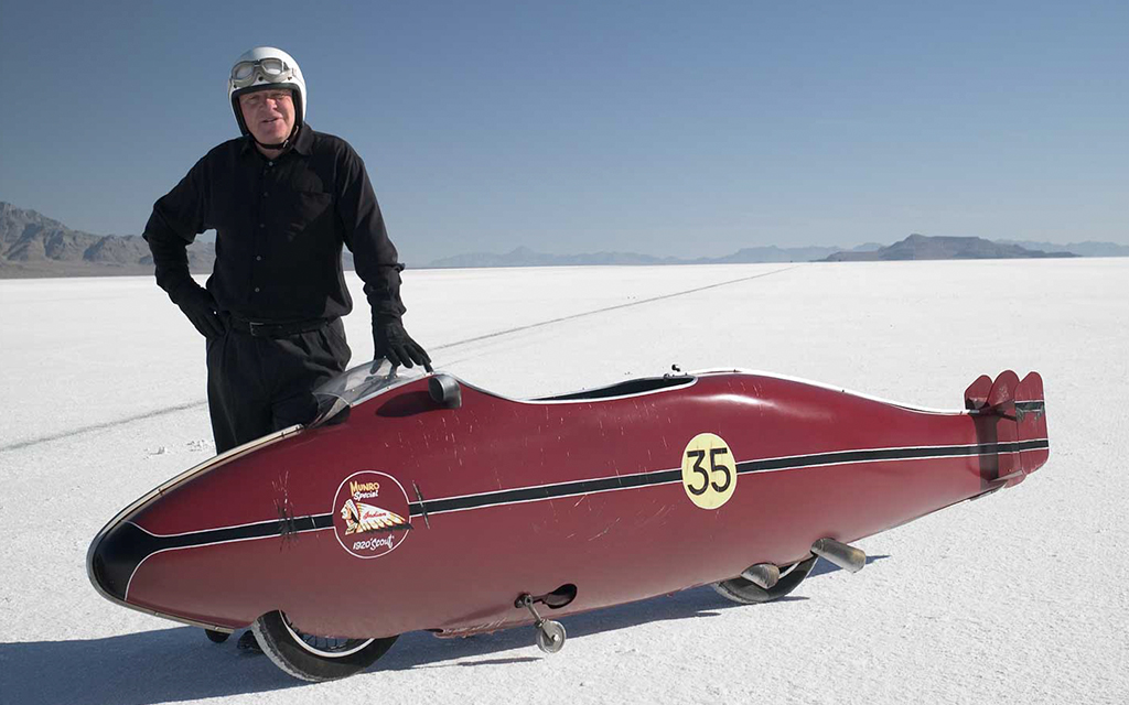 Image from the The World's Fastest Indian movie where Herbert James is standing right next to his red vehicle in the middle of a salt flat