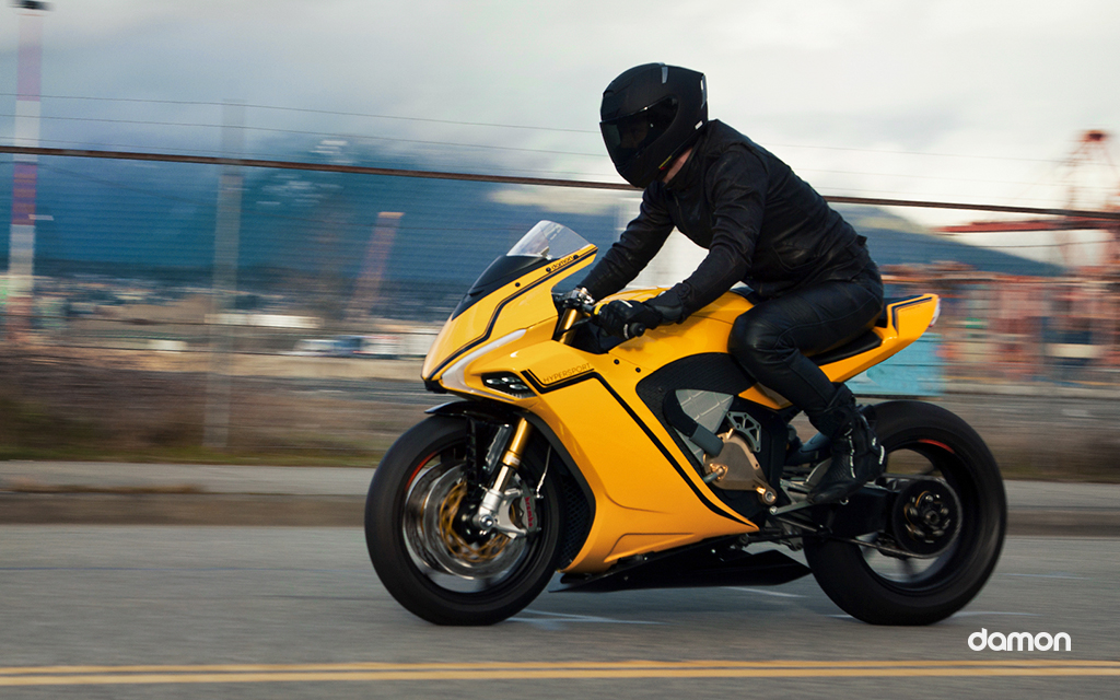 Motorbike rider wearing black gear riding a yellow Damon HyperSport on a highway