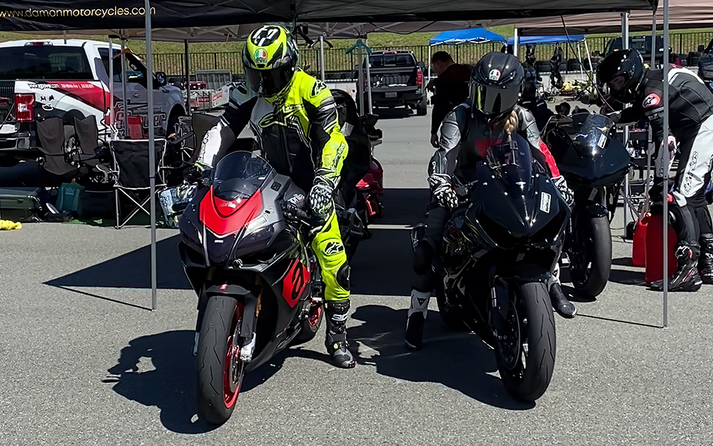 Men and women bike riders ready to start to drive their sport motorbikes at a motorcycle track day event.