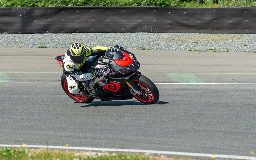 Rider wearing white and green motorcycle gear riding his black and red sport bike at fast velocity on a road