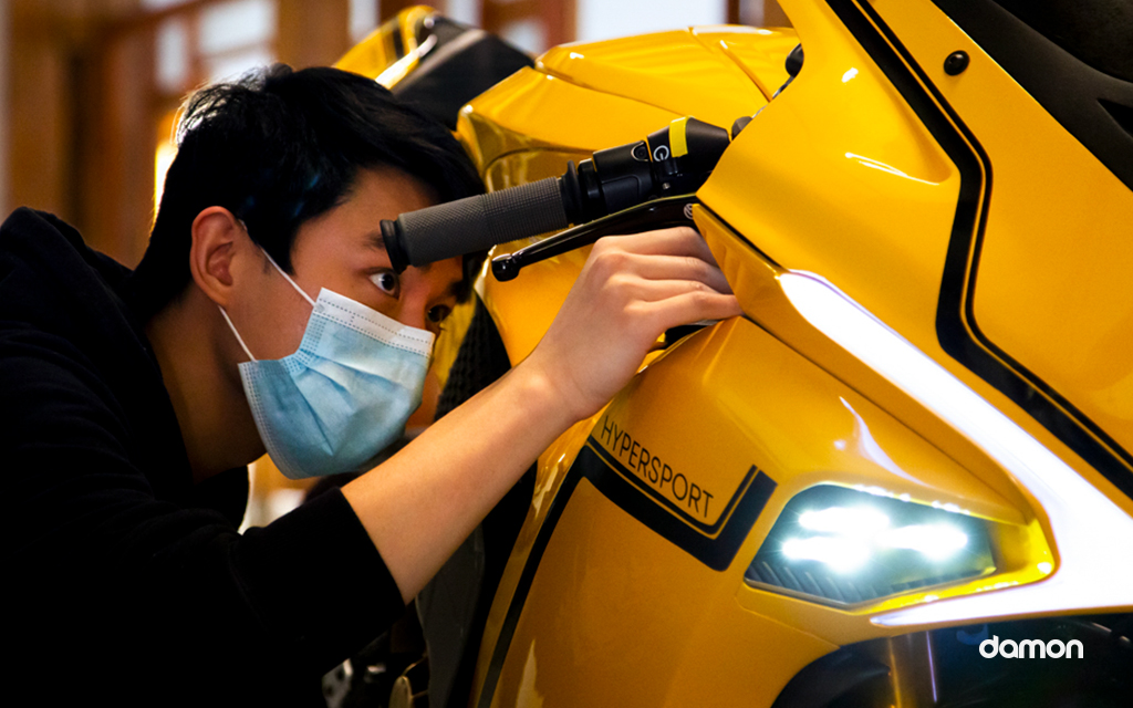 A men looking at the handlebar of a yellow Damon Hypersport