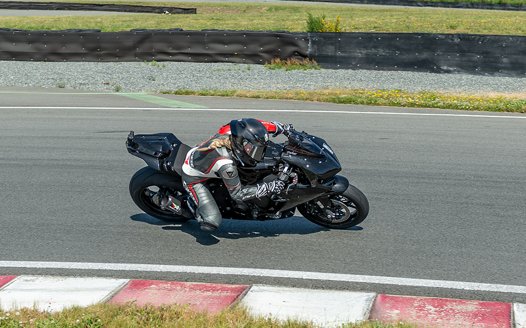Amber Spencer, VP of Customer Development, driving a black sport motorcycle on a raceway in a sunny summer day