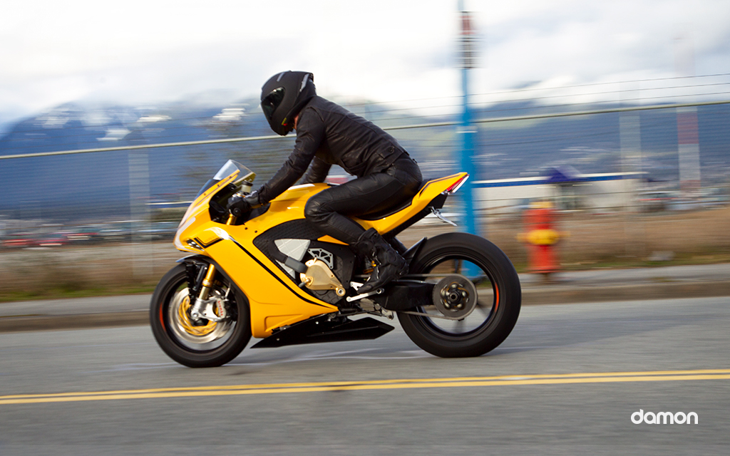 Motorcycle driver on a yellow Damon's HyperSport on highway